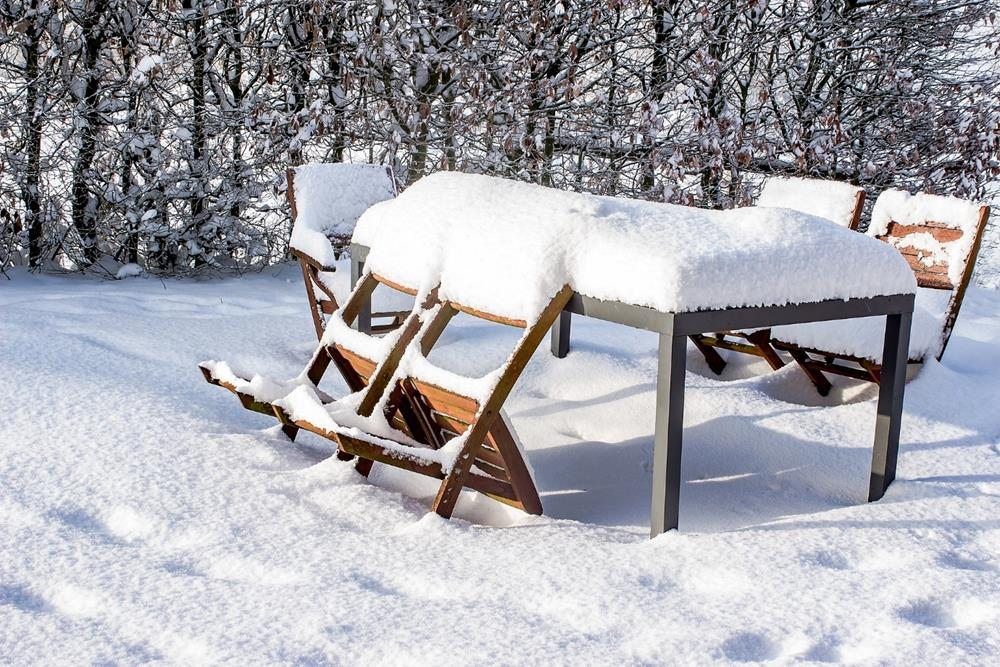 A bench covered in snow  Description automatically generated